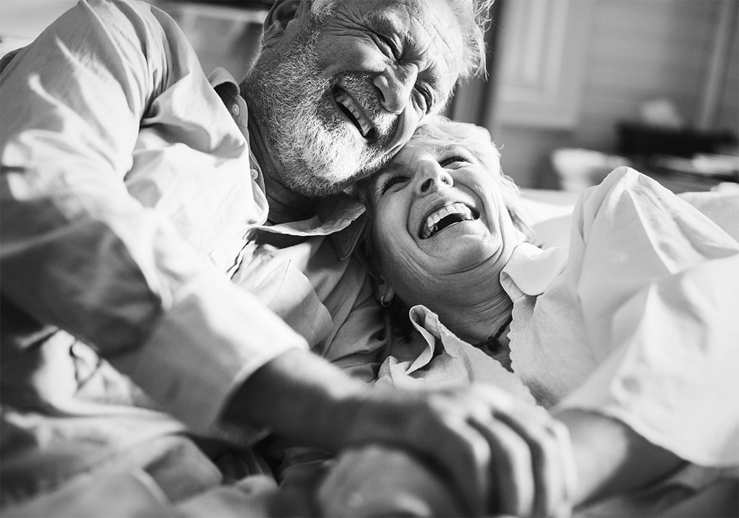 elderly couple holding hands and laughing